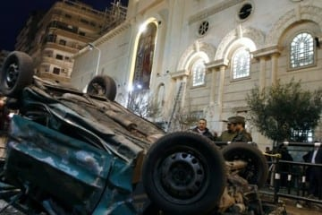 Policemen stand beside the wreckage of a car after a bomb blast outside the Coptic Orthodox church in Egypt's northern city of Alexandria