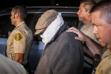 Unidentified person is escorted out of Nakoula Basseley Nakoula's home by Los Angeles County Sheriff's officers in Cerritos, California