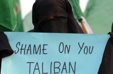 "A Pakistani veiled activist of an Islamic Sunni Tehreek party carries a placard during a protest against the assassination attempt by Taliban on child activist Malala Yousafzai, in Islamabad on October 14, 2012.  A Pakistani schoolgirl shot in the head by the Taliban in retaliation for her campaign for the right to education, is making ""slow and steady progress"" in her recovery, the military said.  AFP PHOTO / AAMIR QURESHI        (Photo credit should read AAMIR QURESHI/AFP/GettyImages)"
